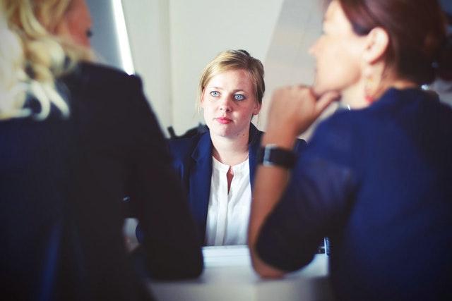 Žena v bielej blúzke a modrom saku s modrými očami pozerá na dve osoby sediace oproti nej.jpg