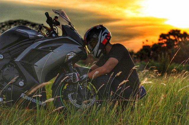 Človek s moto-prilbou opravuje svoju motorku na lúke, Kawasaki