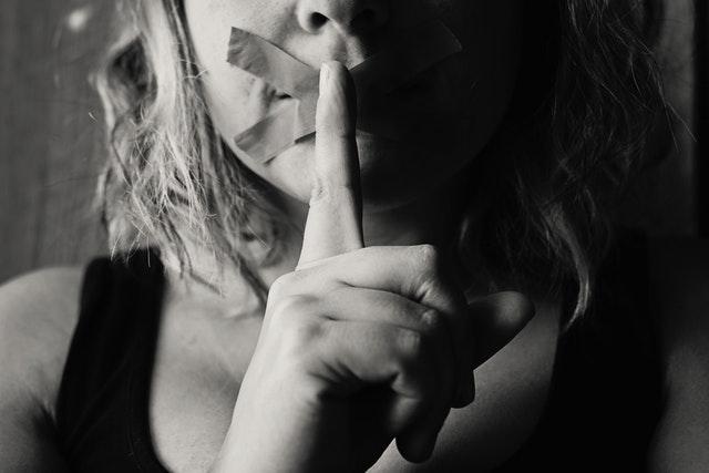 Žena s prelepenými ústami, pred ktorými drží prst.jpg
