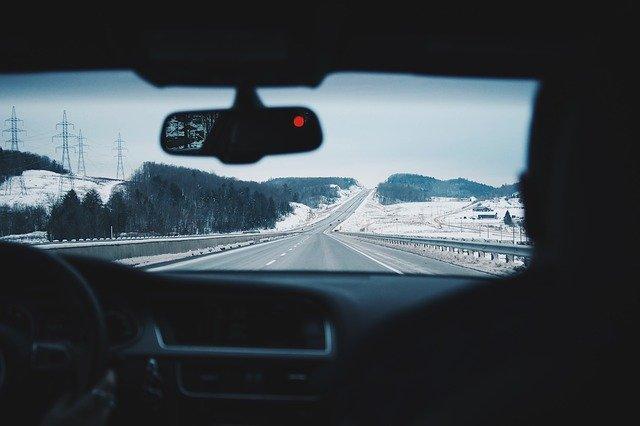 Záber z auta na zasneženú krajinu a diaľnicu.jpg